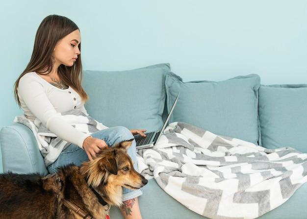 Frau zu hause, die am laptop arbeitet, während sie ihren hund während der pandemie streichelt