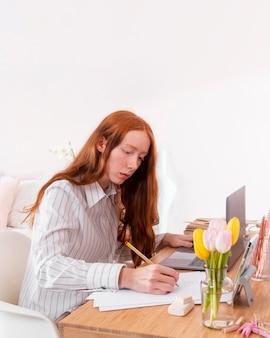 Frau zu hause, die am laptop arbeitet