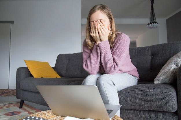 Frau zu hause, die augen mit den händen, denkend schließt. laptop auf dem tisch