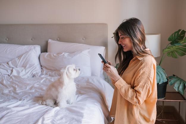 Frau zu hause, die ein foto mit handy ihres hundes macht.