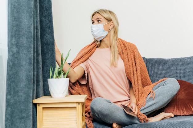 Frau zu hause, die medizinische maske trägt und durch die vorhänge draußen während der pandemie schaut