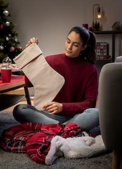 Frau zu hause, die riesige socken vorbereitet, damit sankt geschenke lässt