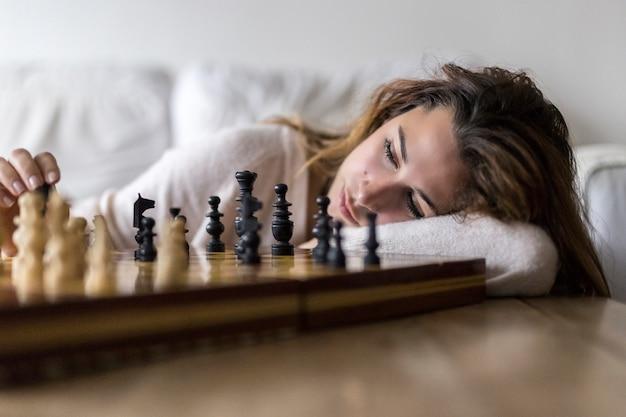 Frau zu hause, die schach alleine spielt