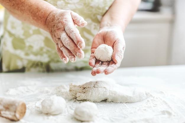 Frau zu hause, die teig zum kochen von nudelpizza oder brot knetet. hausmannskost-konzept. lebensstil
