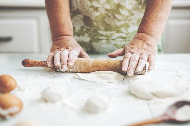 Frau zu hause, die teig zum kochen von nudelpizza oder brot knetet.