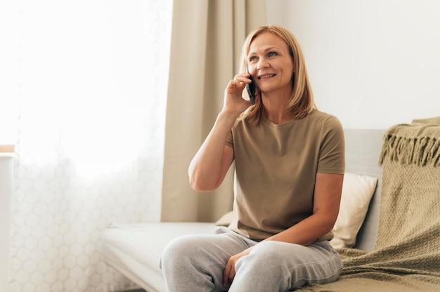 Frau zu hause, die während der quarantäne am telefon spricht