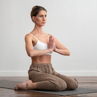 Frau zu hause, die yoga auf matte praktiziert