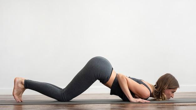 Frau zu hause, die yoga auf matte tut