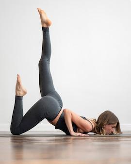 Frau zu hause, die yoga macht