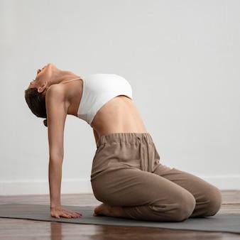 Frau zu hause, die yoga praktiziert