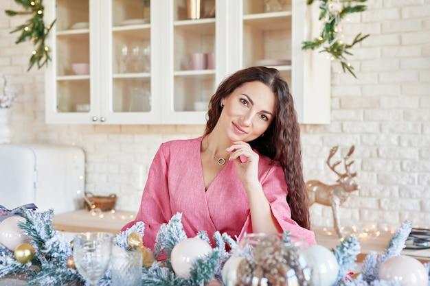 Frau zu hause für weihnachten. frau, die sich zu hause vorbereitet. lächelnde frau im rosafarbenen kleid in der küche. weiße küche interieur. moderne küche mit tisch und geschirr. küche in luxusvilla.