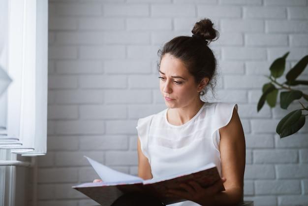 Frau zu hause hält notizbuch, das geschäft von zu hause aus arbeitet.
