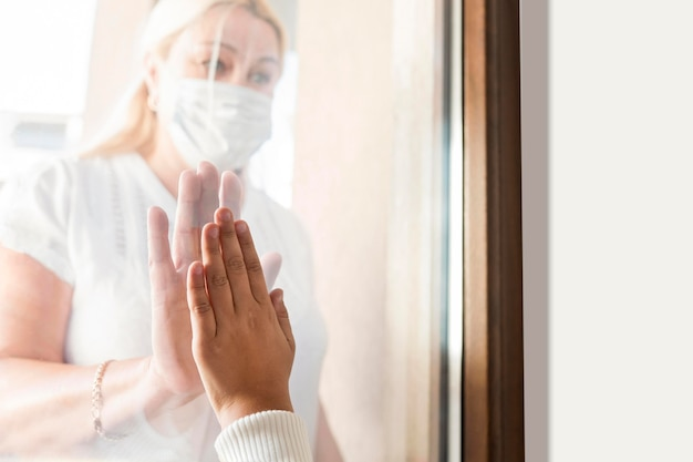 Frau zu hause in quarantäne mit medizinischer maske hinter fenster