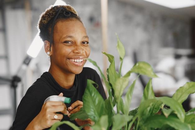Frau zu hause. mädchen in einem schwarzen pullover. afrikanerin im büro. person mit blumentopf.