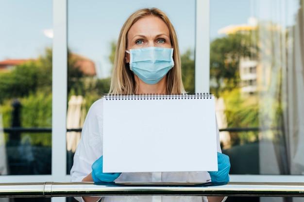 Frau zu hause mit medizinischer maske und handschuhen, die notizbuch halten