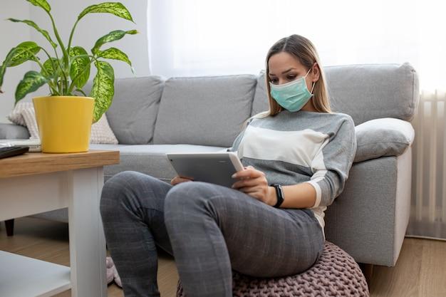 Frau zu hause mit medizinischer maske unter verwendung der tablette