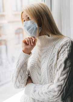 Frau zu hause mit medizinischer maske während der pandemie, die durch das fenster schaut