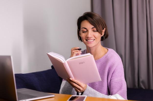 Frau zu hause mit notizblock notizbuch, das über pläne nachdenkt