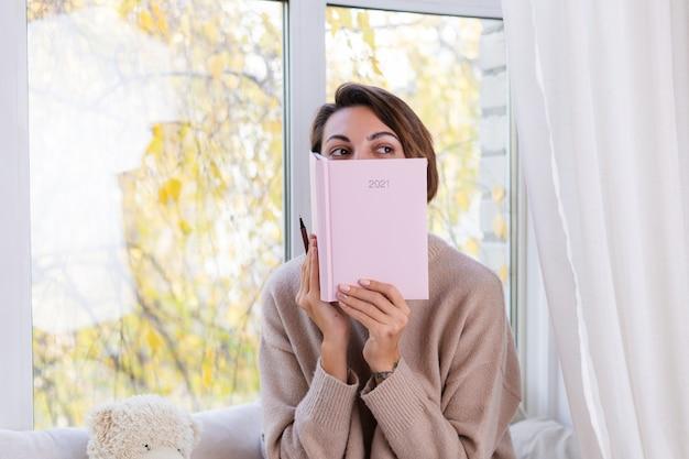 Frau zu hause mit notizbuch sitzen auf der fensterbank in bequemem pullover und warmen wollsocken, kalter herbst außerhalb des fensters