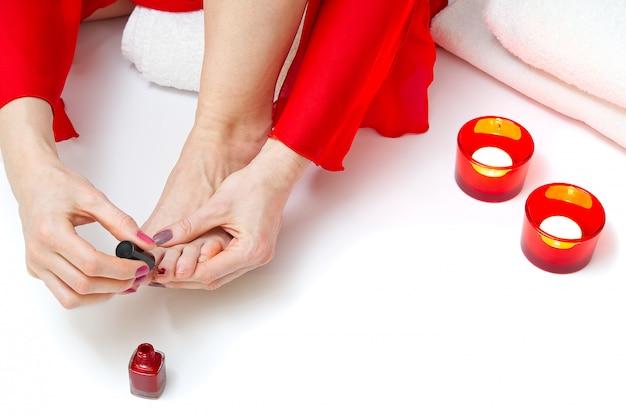 Frau zu hause spa macht pediküre zu sich selbst, nahaufnahme.