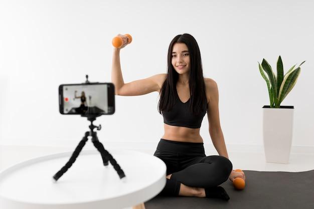 Frau zu hause vlogging mit smartphone während des trainings