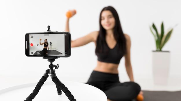 Frau zu hause vlogging während des trainings mit smartphone