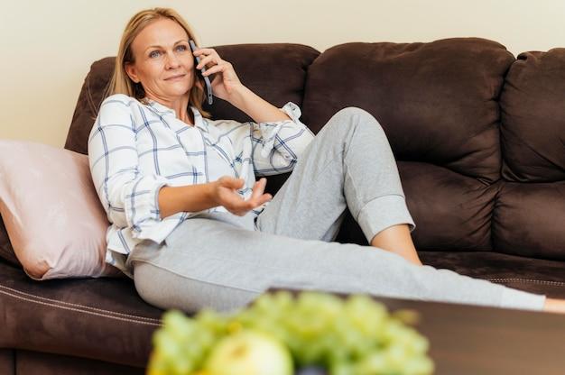 Frau zu hause während der quarantäne, die auf smartphone spricht
