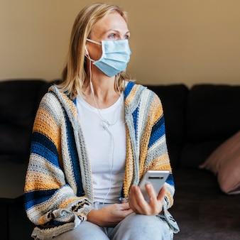 Frau zu hause während der quarantäne mit medizinischer maske und smartphone