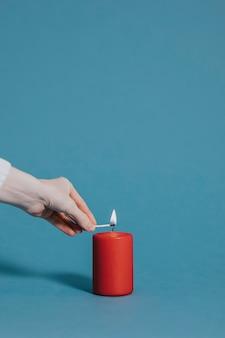 Frau zündet eine rote kerze