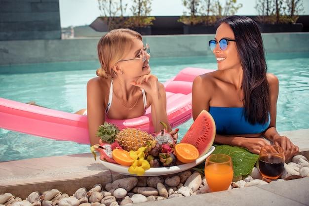 Frau zwei, die auf tropischem luxusferienhaus mit großen platten mit verschiedenen geschmackvollen süßen exotischen früchten im pool sich entspannt