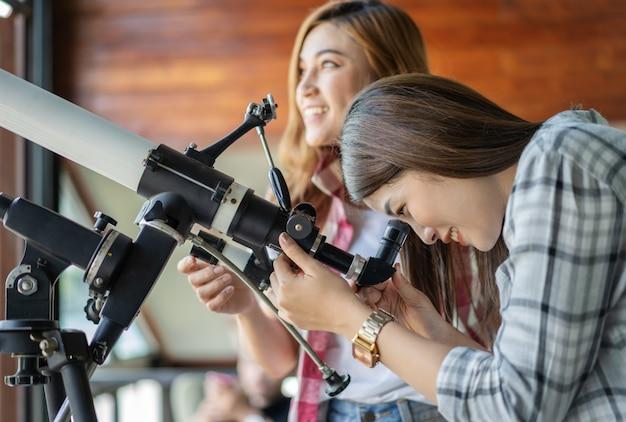 Frau zwei, die durch teleskop schaut