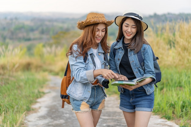 Frau zwei, die richtung auf standortkarte beim reisen sucht