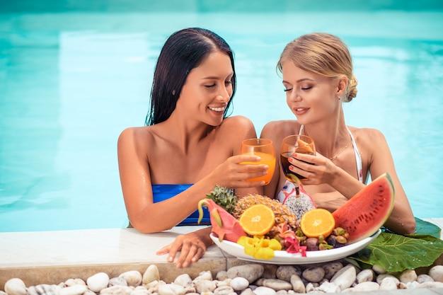 Frau zwei, die sich nahe auf tropischen luxusferien mit großen platten mit verschiedenen geschmackvollen süßen exotischen früchten im pool entspannt