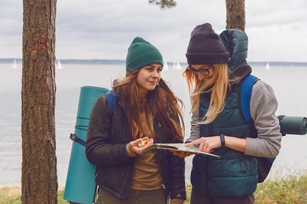 Frau zwei mit dem modischen blick, der richtung auf standortkarte beim reisen an der wilden natur sucht