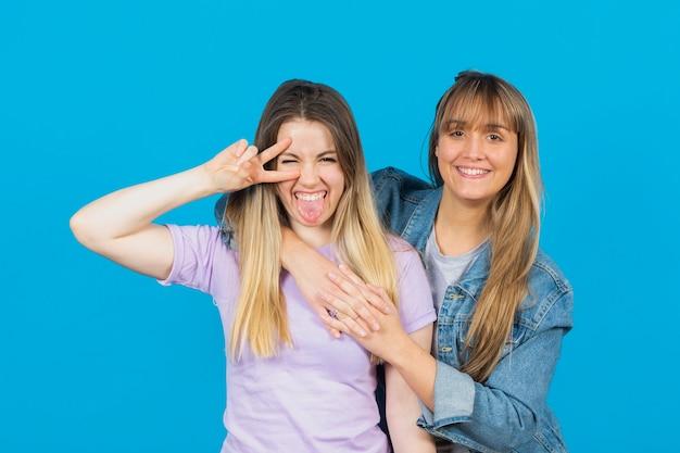 Frau zwinkert der kamera zu und umarmt ihre freundin