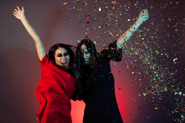 Frauen als hexen verkleidet mit konfetti