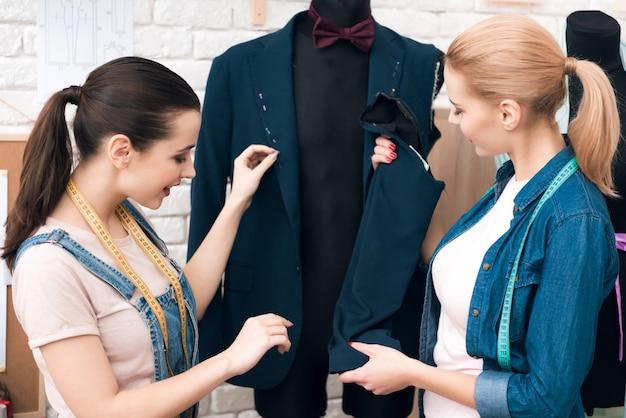 Frauen an der kleiderfabrik, die neue mannanzugsjacke desining ist.