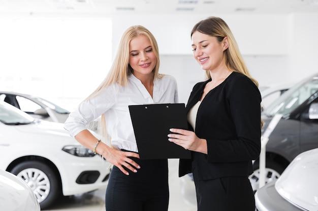 Frauen an der verkaufsstelle, die klemmbrett betrachtet