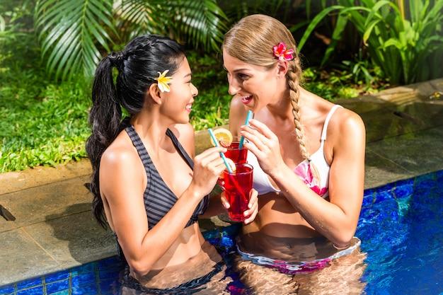 Frauen an trinkenden cocktails des asiatischen hotelpools