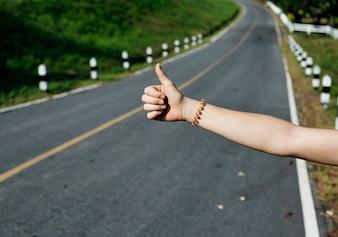 Frauen-Anhalter, der auf der Straßenseite nahe dem zerbrochenen Auto wandert