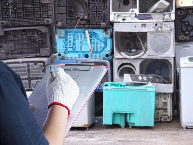 Frauen arbeiten beim recycling von elektronik für müllanlagen. waschmaschinenabfälle sind alte, gebrauchte und veraltete elektronische geräte, die in der fabrikindustrie recycelt werden sollen.