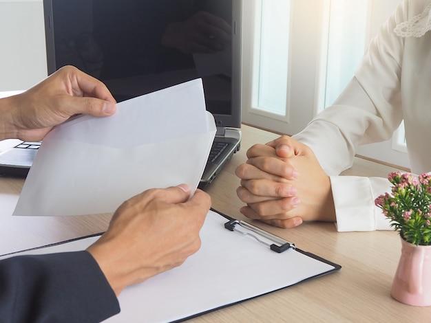 Frauen arbeiten ein kündigungsschreiben an die mitarbeiter der angst aus.