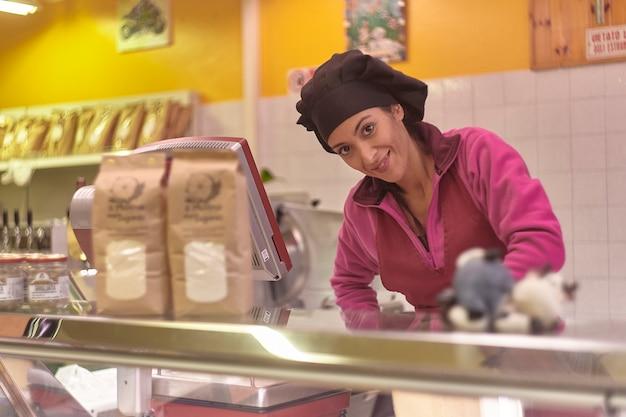 Frauen arbeiten in der kühltheke der metzgerei und nehmen fleischstücke an