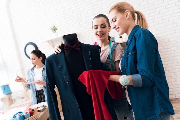 Frauen arbeiten mit anzug und farbe zusammen.