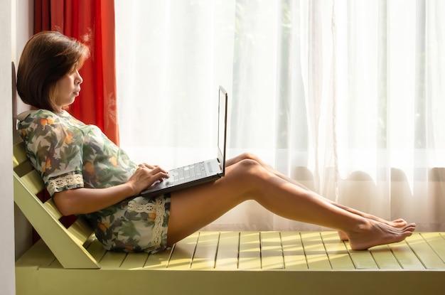 Frauen arbeiten mit notizbüchern auf dem holzbett hintergrund weiße vorhänge und tageslicht.