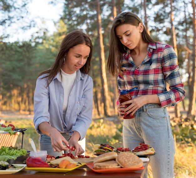 Frauen arrangieren essen auf dem tisch, damit freunde mitmachen können