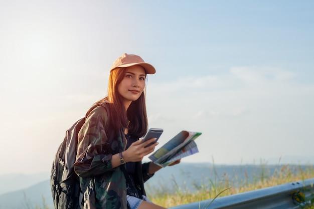 Frauen asiatisch mit hellem rucksack, der eine karte betrachtet. ansicht von der rückseite des touristenreisenden auf berg, weibliche hände unter verwendung des smartphones, das gerät hält