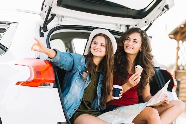 Frauen auf autokofferraum mit der karte, die weg schaut