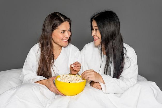 Frauen auf dem bett popcorn essend