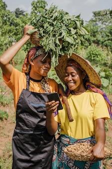 Frauen auf dem land, die zusammen ein telefon durchsuchen